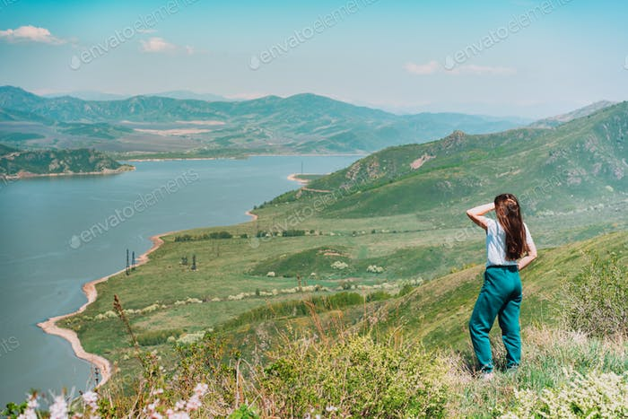 Young woman standing against blue sea and mountains background East Kazakhstan
