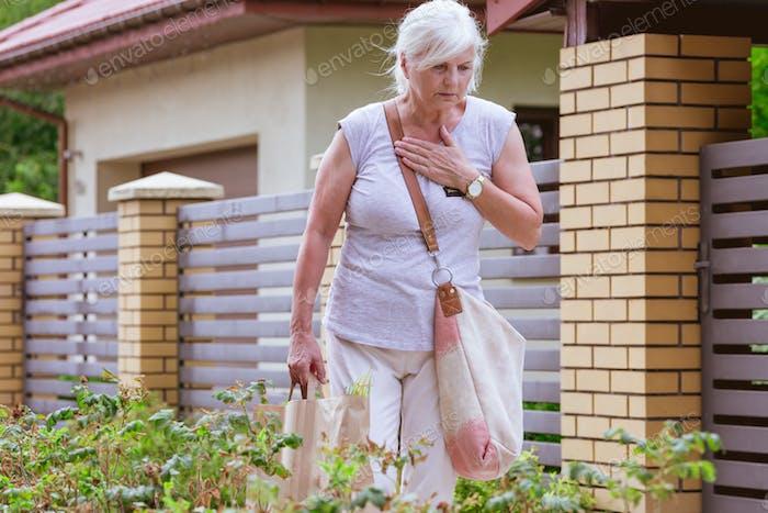 Senior Frau hält ihre Brust, während sie auf der Straße stehen, Herzinfarkt-Konzept