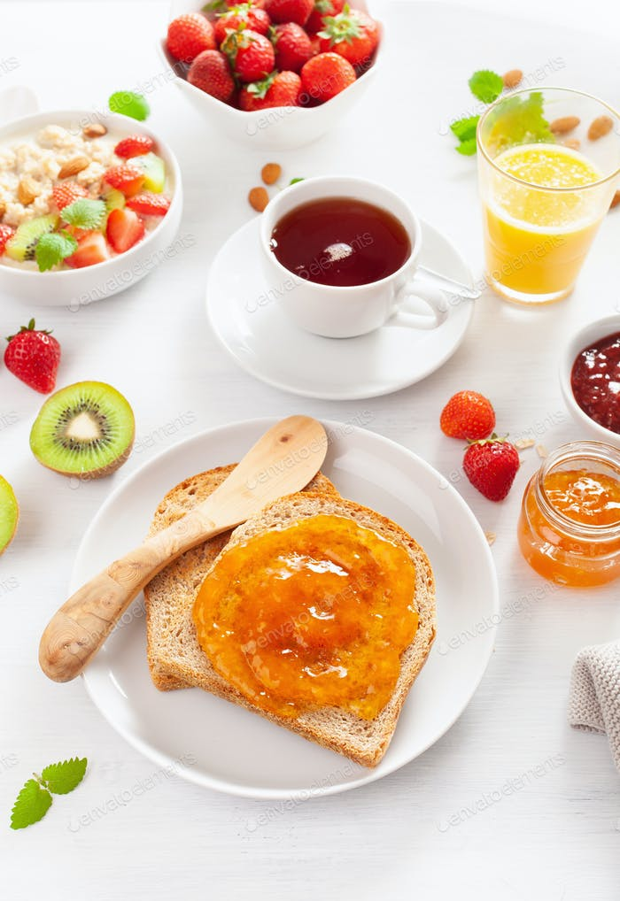 healthy breakfast with toast, porridge, strawberry, nuts, jam an