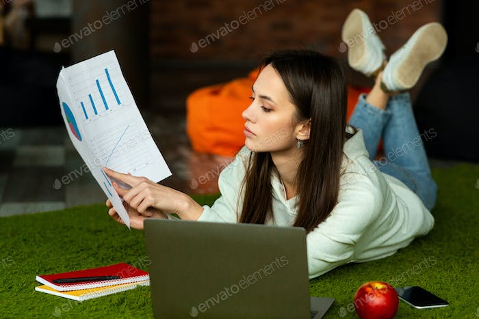 Freelancer millennial woman shows charts online remotely