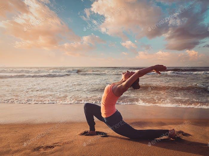 Sportlich fit Frau praktiziert Yoga Anjaneyasana am Strand auf Sonnenuntergang