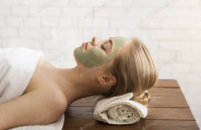 Millennial woman in spa salon with mask on face