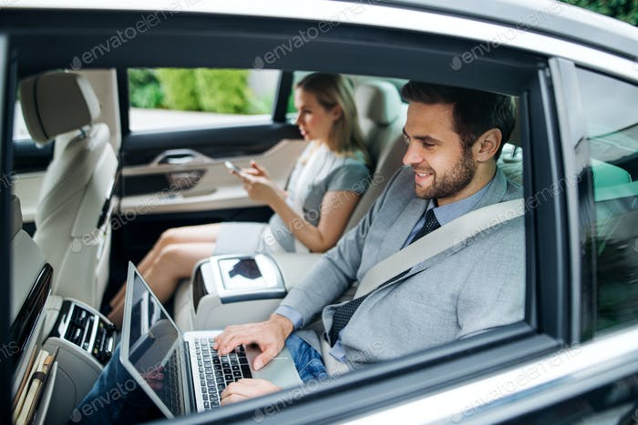 Business couple with laptop sitting on back seats in car, working