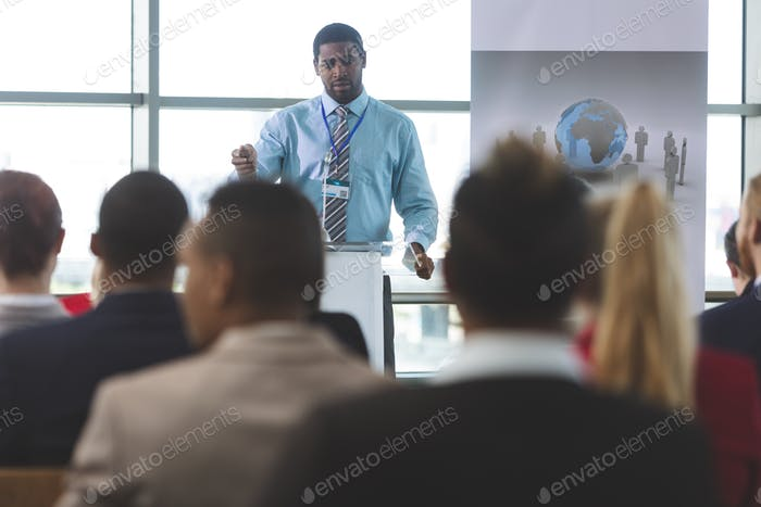 African-American businessman speaker speaking in a business seminar in modern office building