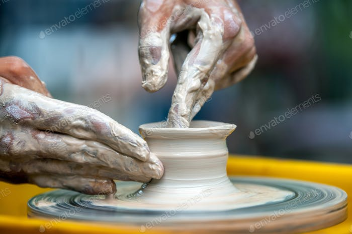 Potter makes pottery dishes on potter's wheel