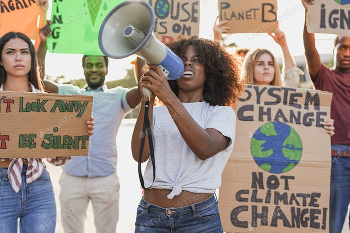 Young multiracial people demonstrate on the street with banner for the climate change