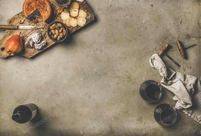 Gleasses of red wine, wine bottle, appetizers on wooden board