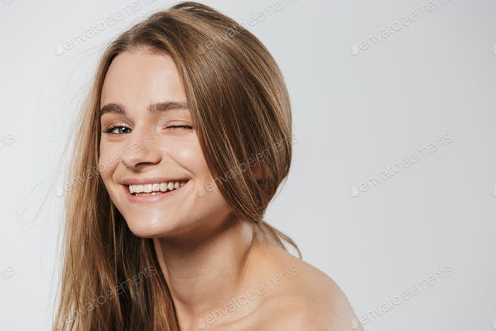 Beauty portrait of young blonde half-naked woman with long hair winking