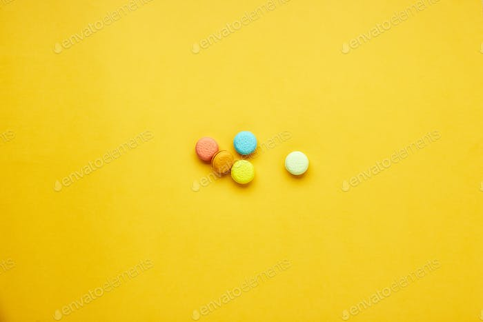 Multicolored macaroon cakes on a yellow background.