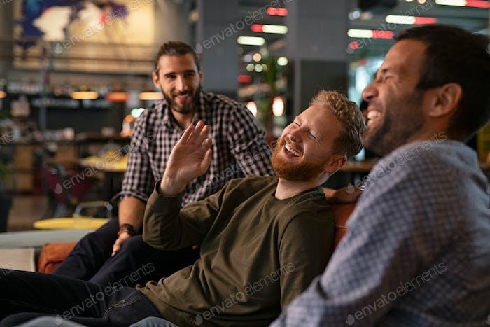 Mid adult men friends enjoying at pub