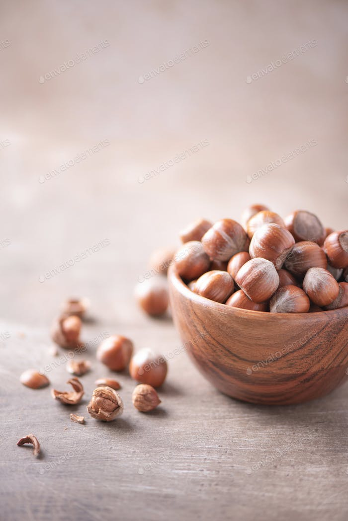 Hazelnuts in wooden bowl on wood textured background. Copy space. Superfood, vegan, vegetarian food