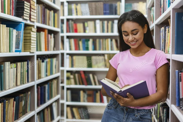 Smiling black girl reading book between bookshelves