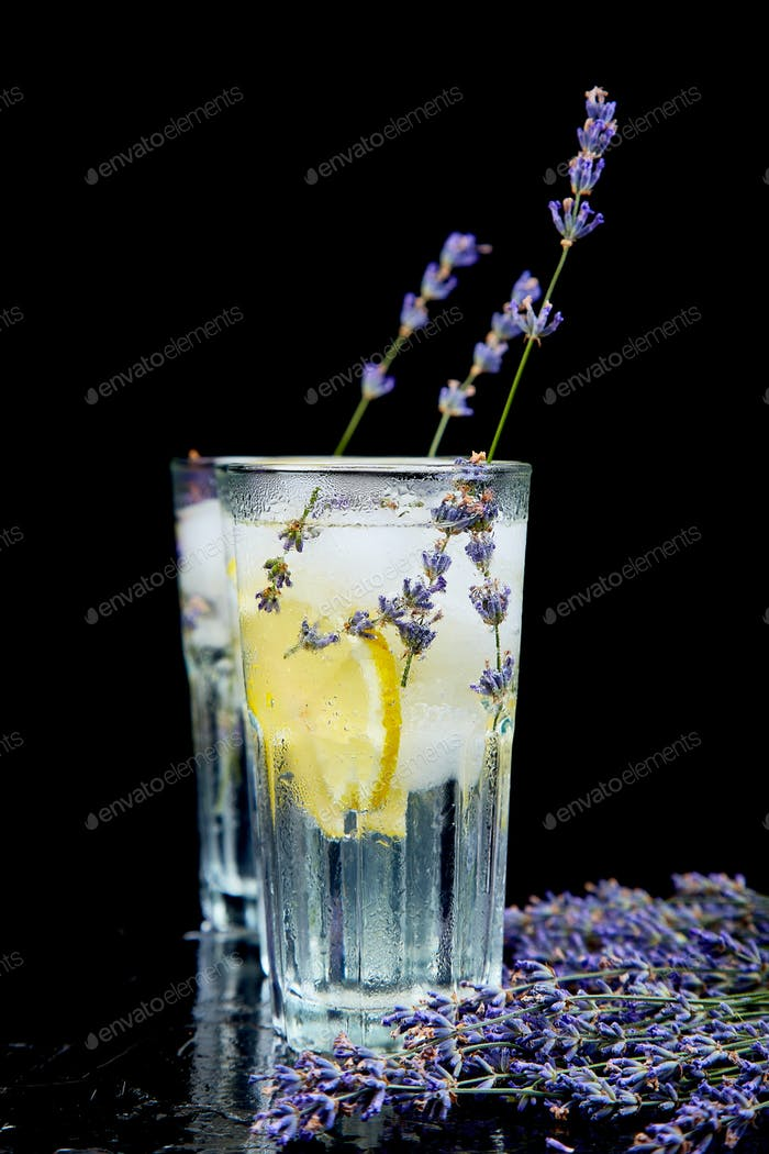 Lavender lemonade with lemon and ice on black background.