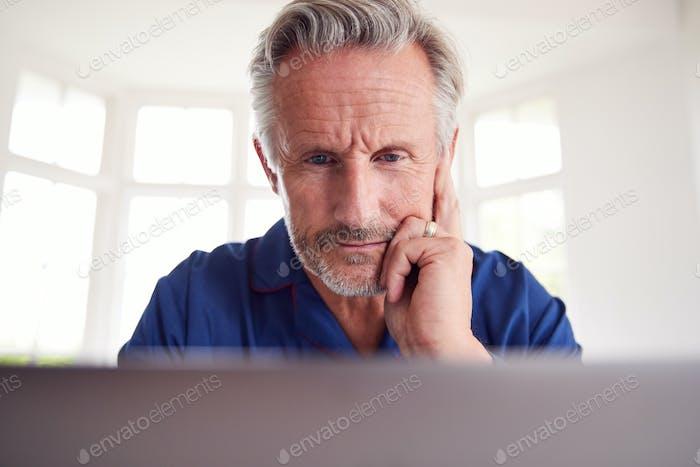 Serious Mature Man Suche nach Informationen Online mit Laptop