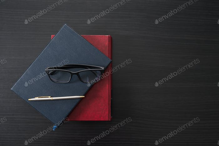 Glasses and book on the wood desk