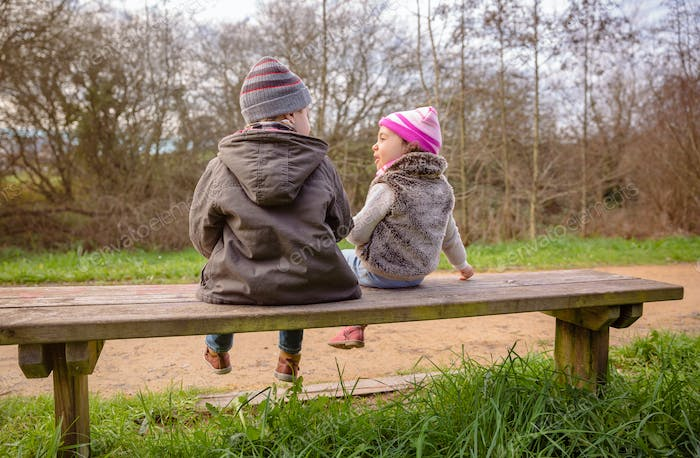 Boy and little girl talking sitting on a bench