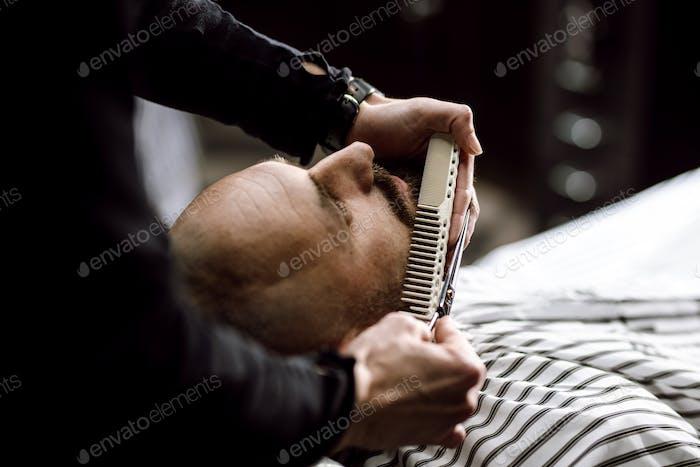 Der Friseur gekleidet in eine schwarze Kleiderschere Bart des brutalen Mannes im stilvollen Friseursalon