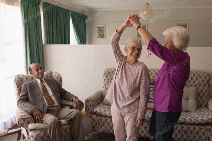 Front view of happy senior friends dancing together while man looking their at home