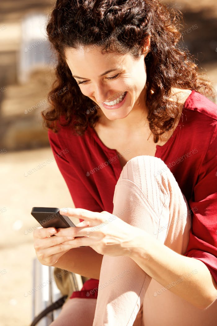 attractive young woman smiling and looking at cell phone