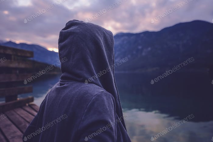 Lonely hooded person standing by the lake