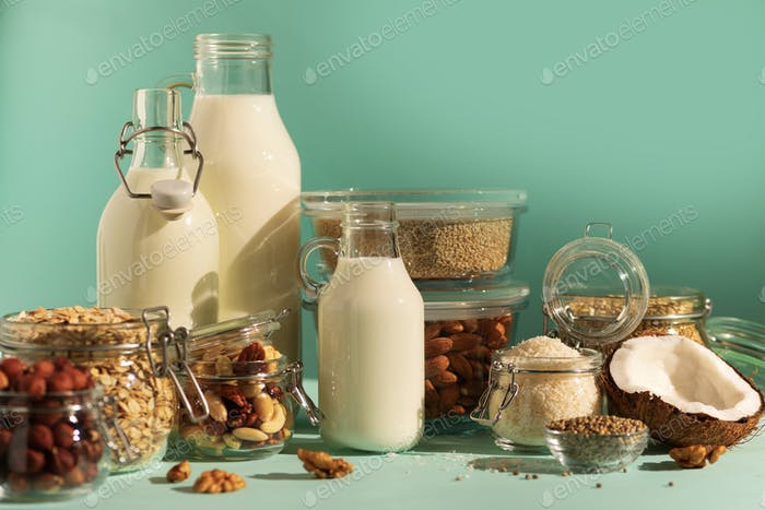 Vegan substitute dairy milk. Glass bottles with non-dairy milk and ingredients over blue background