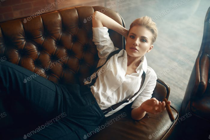 Woman with cigar lying on couch, retro fashion
