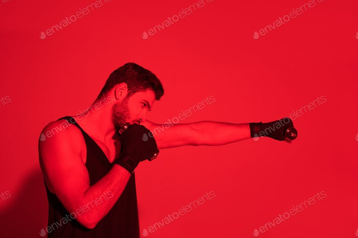 side view of fighter making hit with hands covered with bandages under red light