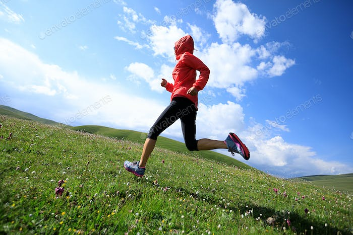 Woman running on grass and flowers in mountain
