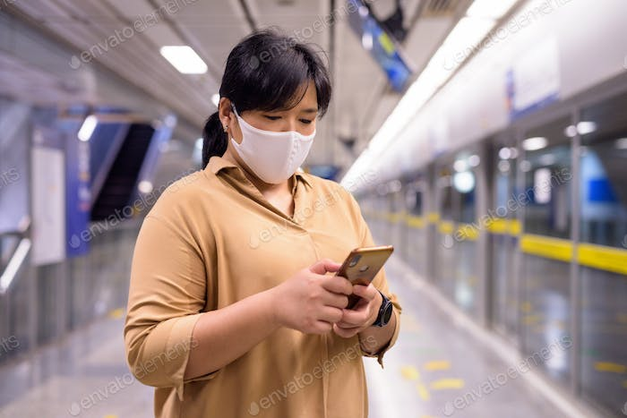 Overweight Asian woman using phone with mask for protection from corona virus outbreak at subway
