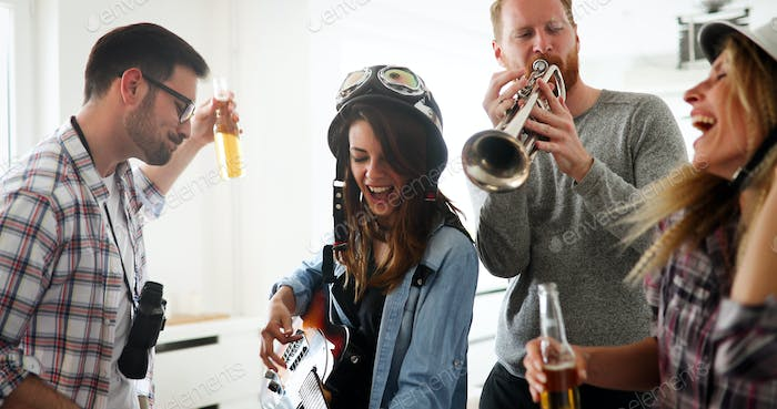 Happy group of friends playing instruments and partying