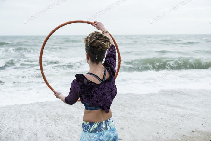 Young woman with brown hair and dreadlocks standing on a sandy beach by the ocean, balancing hula