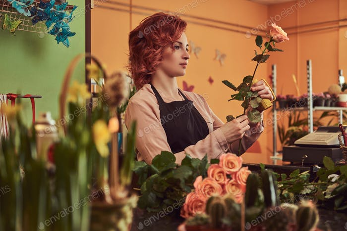 Charmante Rothaarige weibliche Floristen tragen Uniform machen eine schöne Blume Komposition