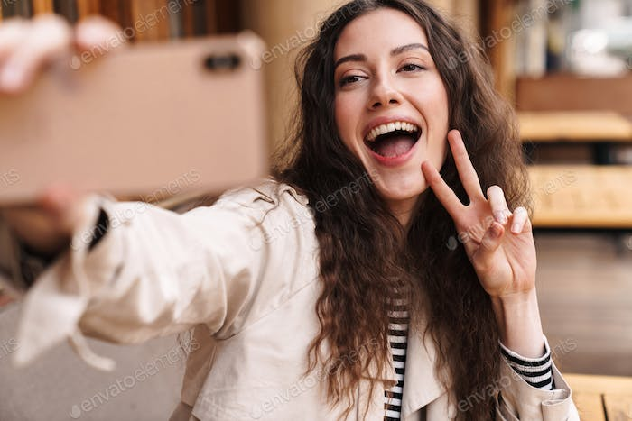 Image of happy woman taking selfie on cellphone and gesturing peace