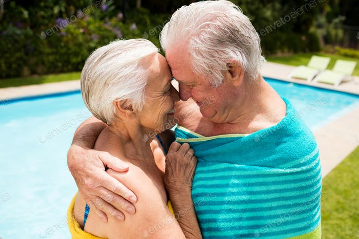 Senior couple embracing each other at poolside