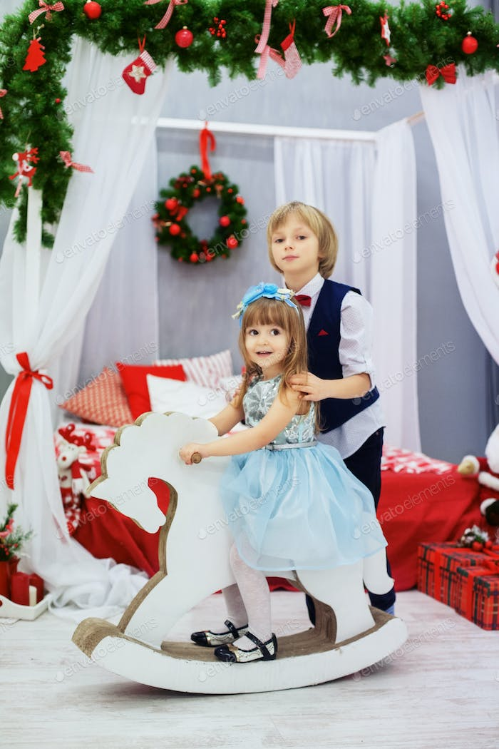 brother and sister playing in the room. The concept of Christmas