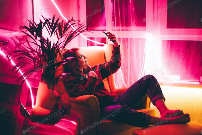 Young woman making video call with smart phone in living room with neon light at home