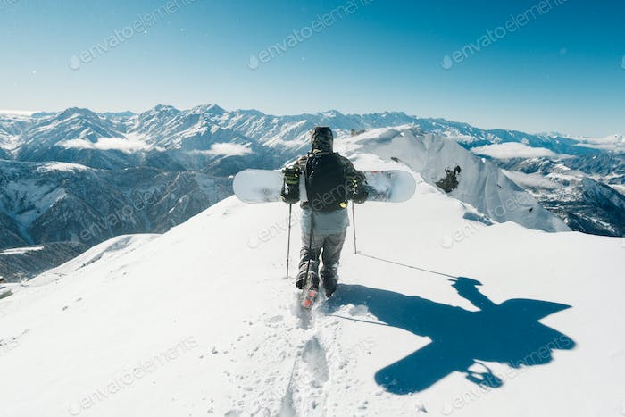 sportsman go with snowboard equipment in the snowstorm
