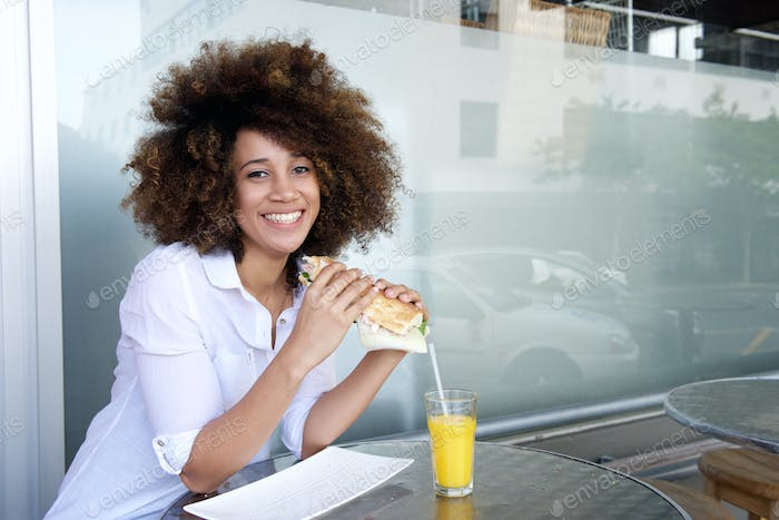 Young african american woman holding sandwich at cafe