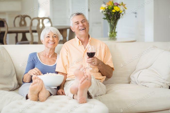 Senior couple having popcorn and glass of wine in living room