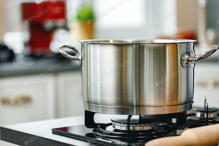 Stainless steel pot on a gas stove in kitchen close up