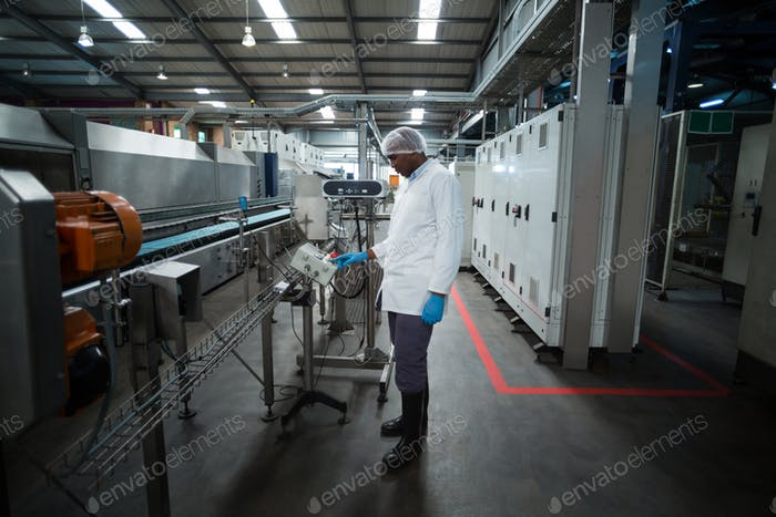 Factory engineer operating machine in factory