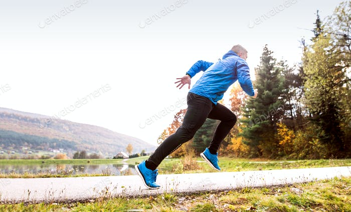 Athlete at the lake running against colorful autumn nature.