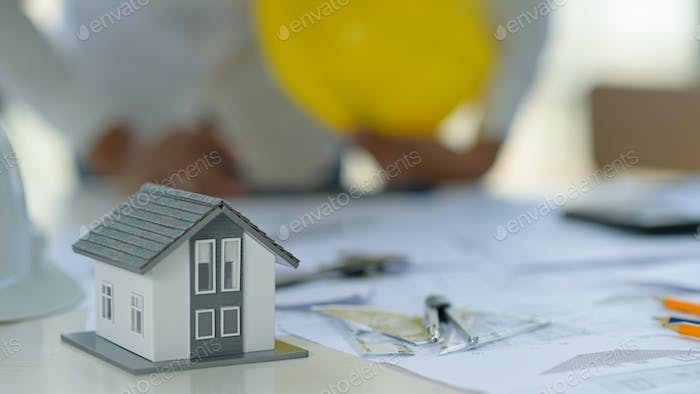 Conceptual home designs, Working spaces with model houses and drawing equipment.