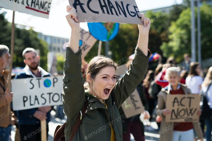 Young woman with placard and poster on global strike for climate change
