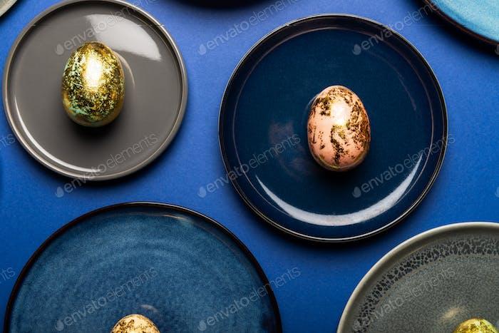 Verschiedene Teller mit Ostereier in Pastellfarben auf blauem Hintergrund