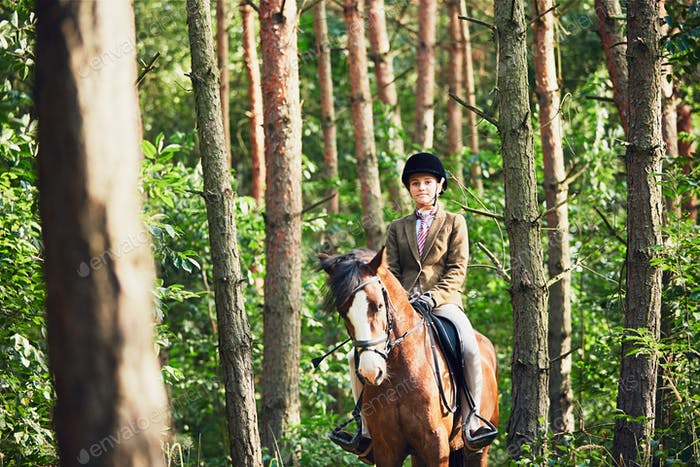 Girl riding a horse in forest