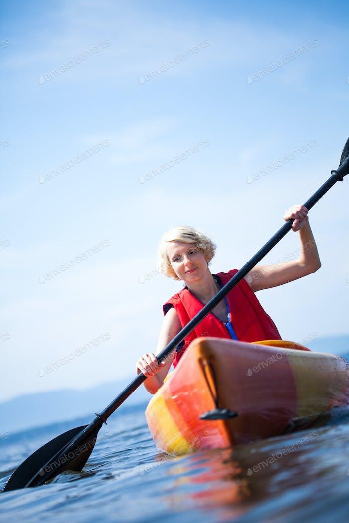 Mujer con chaleco de seguridad kayak solo en un Mar tranquilo