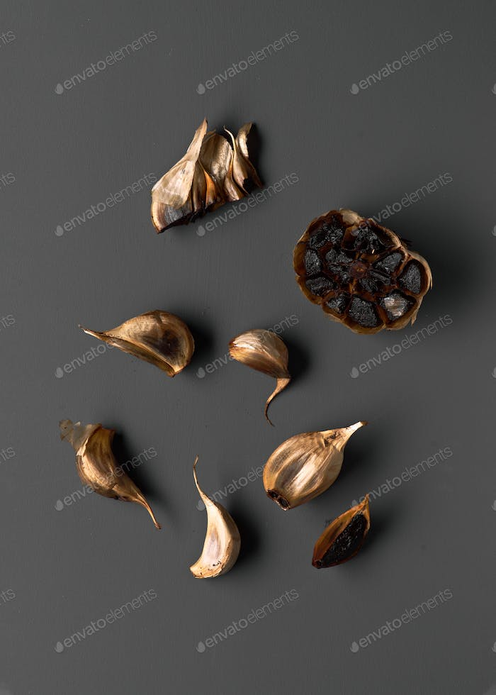 black garlic and old knife on gray board, top view
