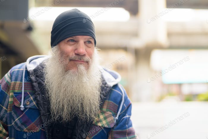 Face of mature handsome bearded man thinking in the city outdoors