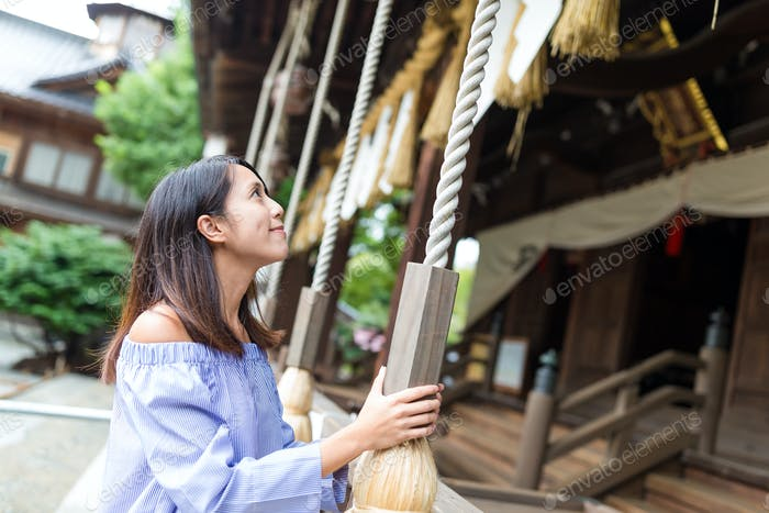 Woman wishing and ringing the bell in Japanese